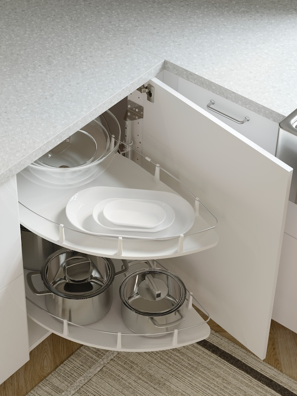 A kitchen with grey worktops and an open corner cabinet in white where an UTRUSTA carousel stores pots, pans and dishes.