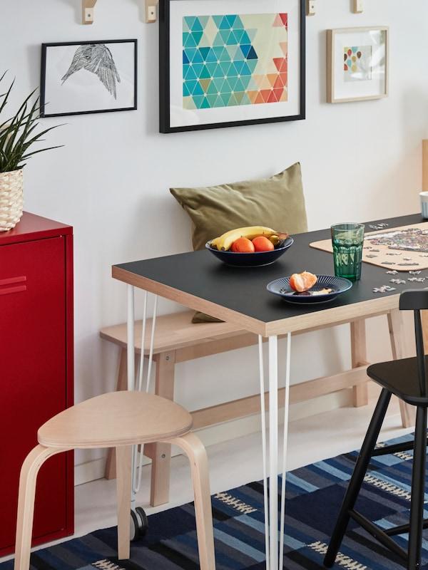 在带白色桌腿的灰色LINNMON 利蒙 桌面后面,白色的墙边摆放着一张NORRÅKER 诺鲁克 桦木长凳,凳子上面放着一个绿色靠垫。