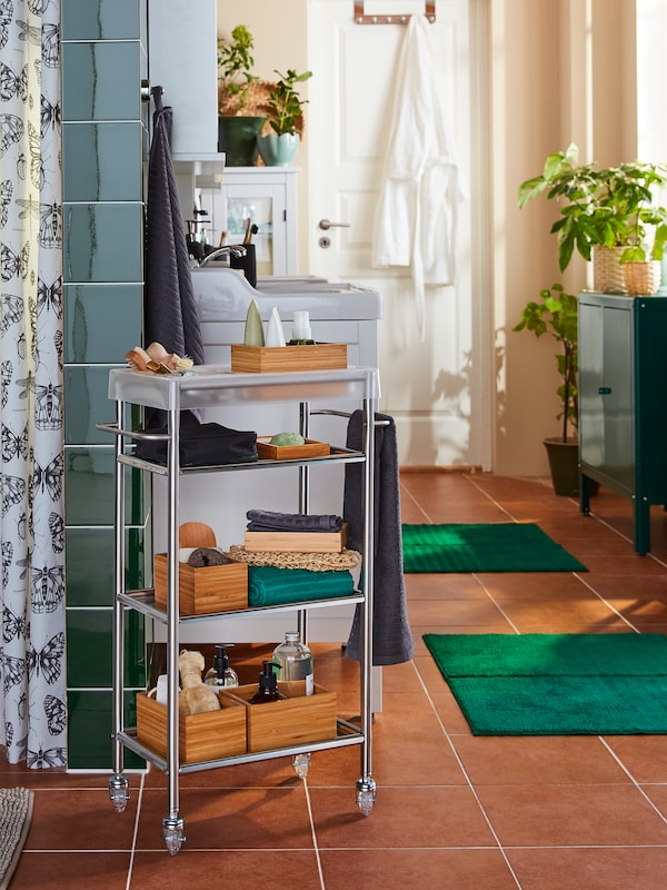 A bathroom with beige walls and brown floors, a GRUNDTAL trolley with bathroom accessories is next to a shower curtain.