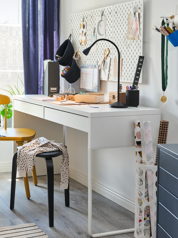 A MICKE desk, an OMTÄNKSAM chair and a KYRRE stool sit in a corner under three wall-mounted SKÅDIS pegboards.