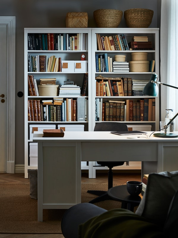 White HEMNES bookcases full of books and boxes, behind a HEMNES white-stained desk with a green ARÖD work lamp.