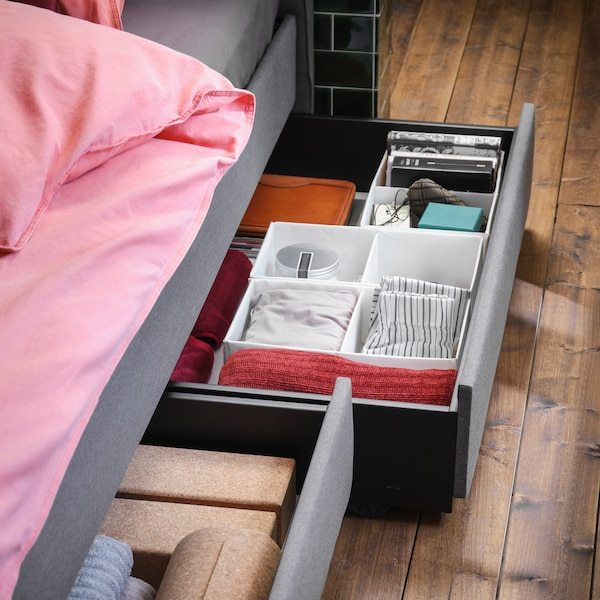 Section of a grey HAUGA bed with pink and grey bed linen, with bed drawers open showing items stored in SKUBB boxes inside.