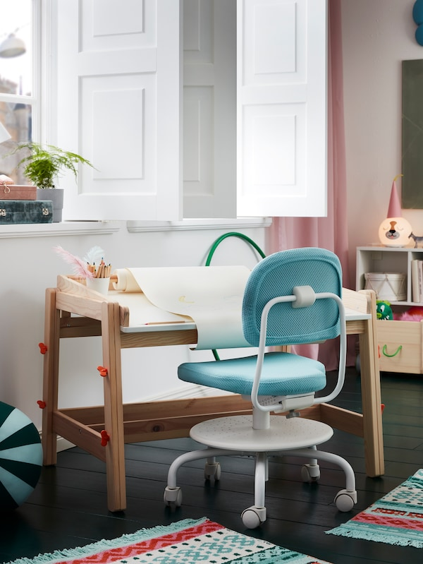窗边放着一张FLISAT 福丽萨特 儿童书桌,上面放着MÅLA 莫拉 画纸卷,桌前还有一张ÖRFJÄLL 奥菲 儿童书桌椅。