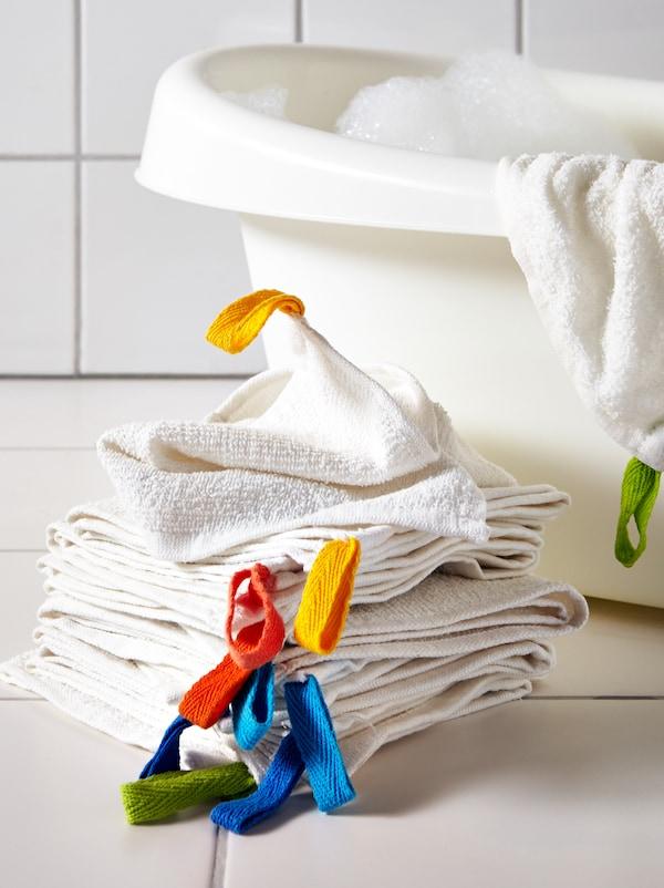 地上放着一叠KRAMA 克力马 小方巾,背后是LÄTTSAM 勒的山 婴儿浴盆。浴盆上还搭着一块小方巾。