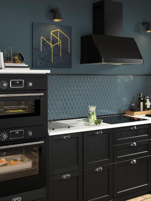 黑色厨房配有蓝色墙面、黑色抽油烟机、白色工作台以及嵌入式微波炉和烤箱。