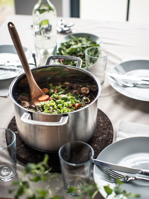 A hot pot containing cooked vegetables is standing on a cork trivet on a set dinner table. A wooden spoon is inside the pot.