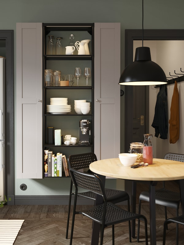 An open shelving unit between two tall cabinets with grey doors, a round wooden table, black chairs and a black pendant lamp.