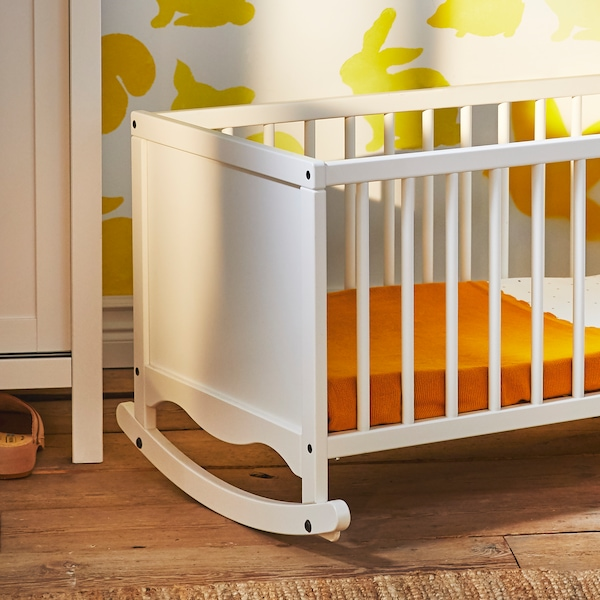 A white SOLGUL cradle with foam mattress covered with a dark yellow blanket.