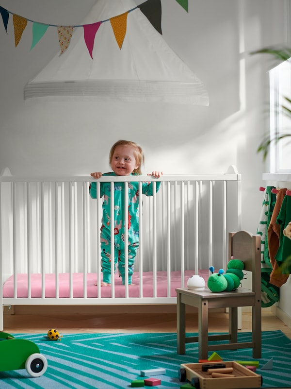 A child stands in a SMÅGÖRA cot. Multicolour bunting hangs on the ceiling above and a SUNDVIK children's chair is in front.
