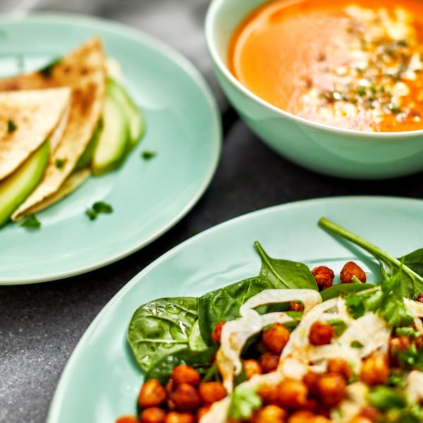 A close-up of two light-green plates and one bowl containing avocado and tortillas, soup and a salad.
