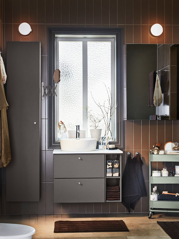 A bathroom with brown tiles, two SVALLIS wall lamps, GODMORGON high cabinet, washstand in dark grey next to a large window.