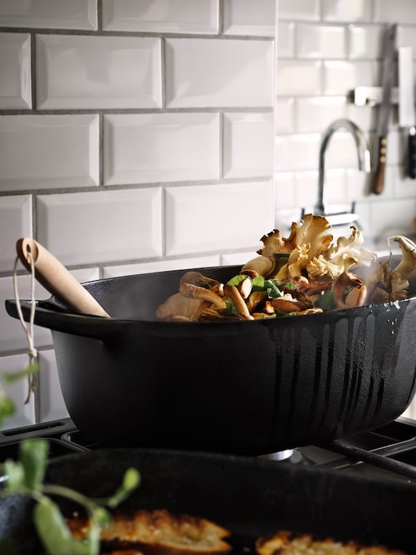 A black casserole with mushrooms inside stands on a gas hob.