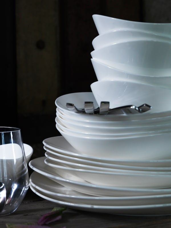 Various sizes of white plates and white serving bowls are stacked on top of each other next to a glass.