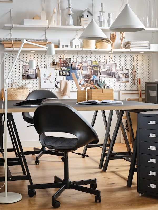 A work room with a work table, floor lamps, diverse items on the table, storage and two black swivel chairs.