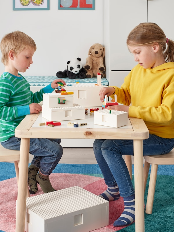 Two children play with LEGO bricks together at a wooden table, attaching LEGO minifigures to two white BYGGLEK boxes.