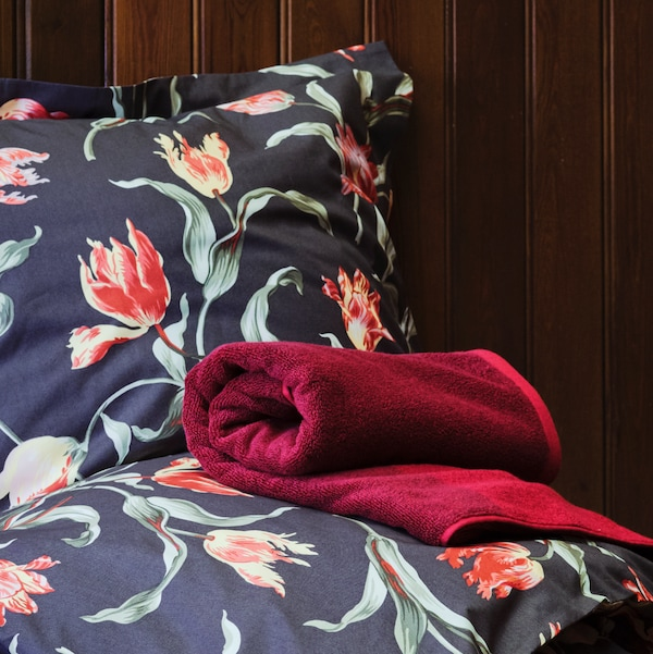ÅLANDSROT bed linen in a grey/floral pattern with a rolled TRATTVIVA dark red bedspread on it, against a wood panelled wall.