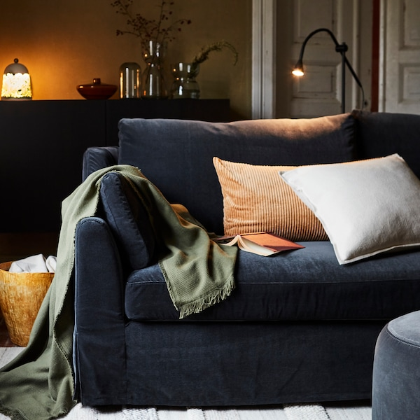Cushions lie on top of a dark grey FÄRLÖV sofa in a living room at night. A throw hangs over the side of the sofa.