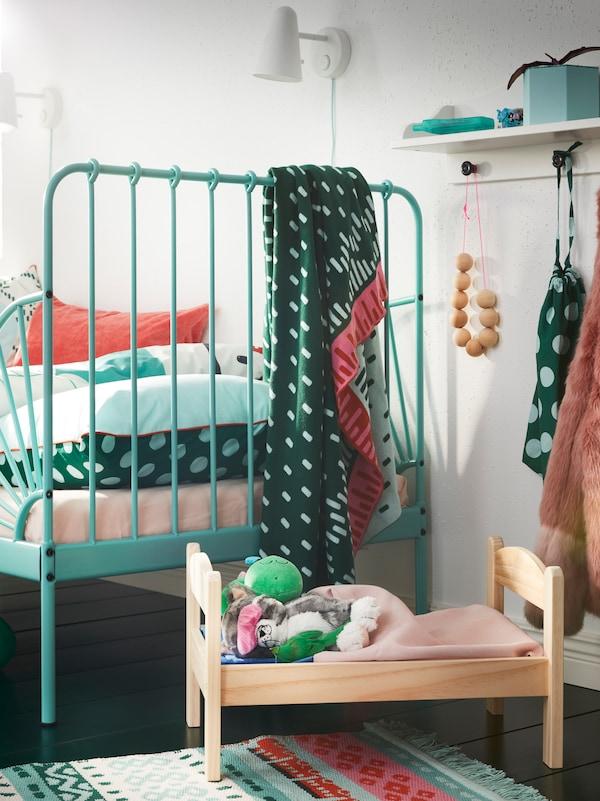 MINNEN 米隆 可加长床旁边是一个搁架,搁架下方放着DUKTIG 杜克迪 实心松木玩偶床,床上躺着盖上被子的毛绒玩具。
