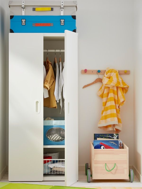 A half-open STUVA/FRITIDS wardrobe stands next to a wall-mounted FLISAT knob rack and a FLISAT toy storage with wheels.