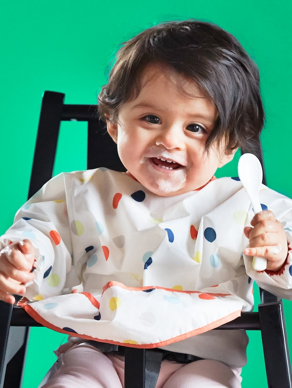 A smiling young child with dark hair wearing a KLADDIG bib and holding a plastic spoon sits in a BLÅMES highchair.
