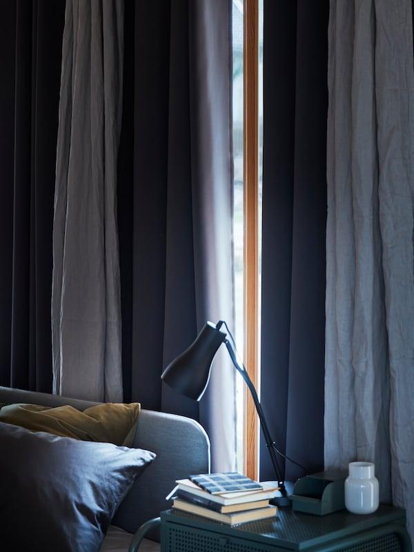 卧室的窗户上装着HANNALILL 汉娜利尔 和HILLEBORG 希尔伯格 窗帘,窗帘略微拉开了一点,一旁的边桌上放着一盏FINNSTAR 费银思达 灯。