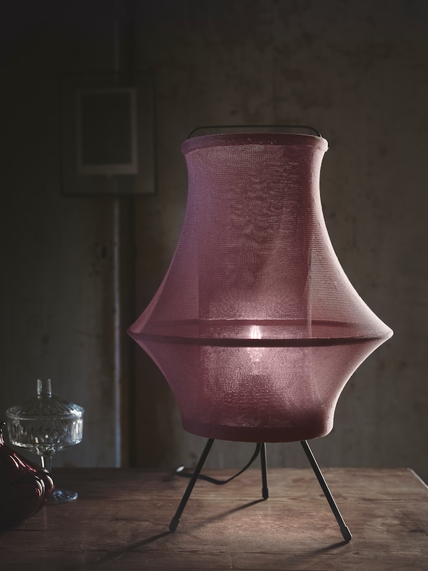 昏暗的房间里,木质桌面上放着一盏独特的灯,带三条支腿,设计充满未来主义风格,灯罩为红色面料。
