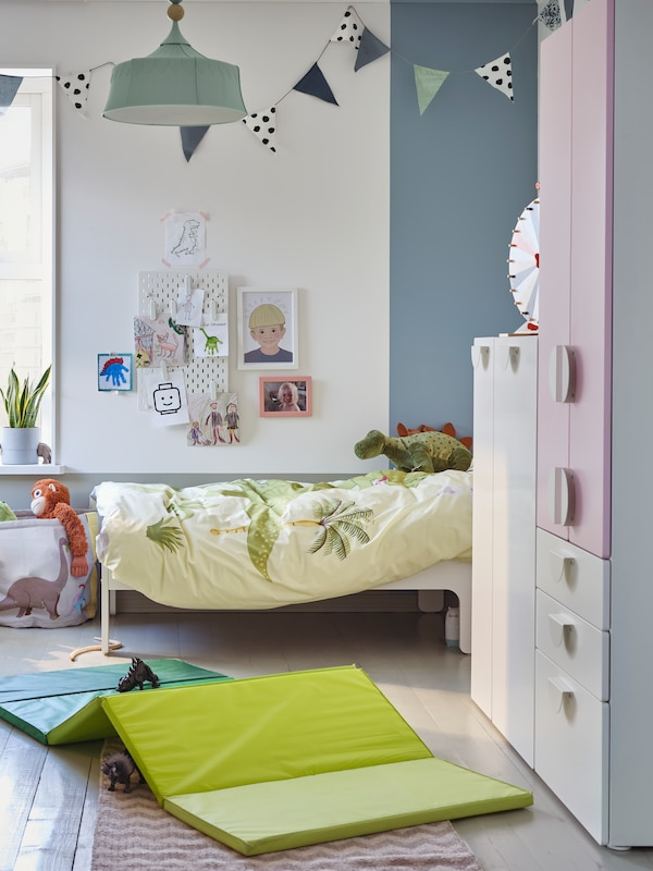 SMÅSTAD storage stands near a SLÄKT extendable bed in a child's room. A PLUFSIG folding gym mat lies on the floor.