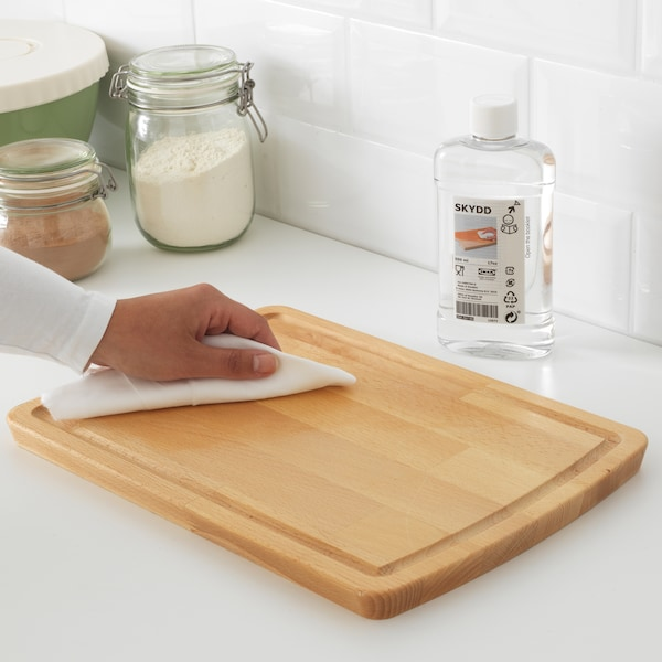 With a cloth, a hand applies SKYDD wood treatment oil to a wooden chopping board in front of a bottle of the product.
