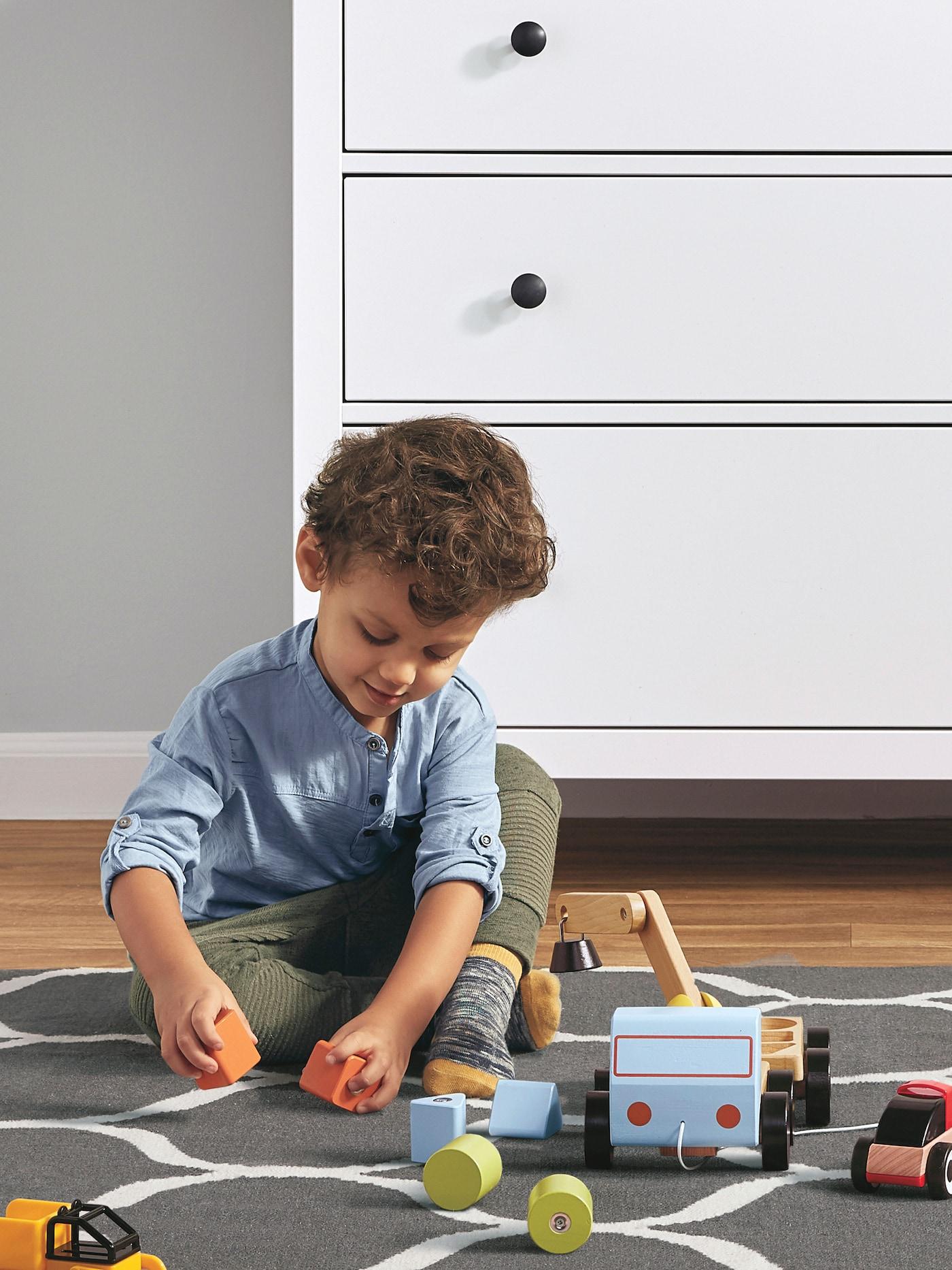 一个身穿蓝色上衣的孩子坐在灰白相间的地毯上玩木制玩具,后面放着白色的HEMNES 汉尼斯 抽屉柜。