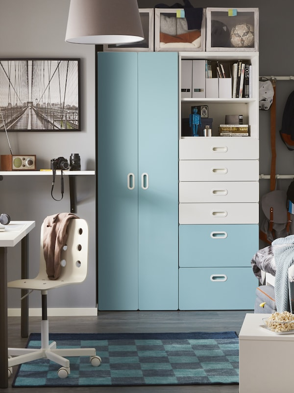儿童房里放着淡蓝色和白色的STUVA 斯多瓦/FRITIDS 福利蒂德斯 衣柜和抽屉柜,前面铺着格纹地毯。