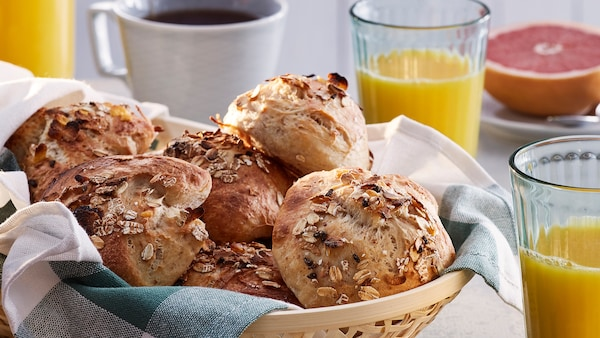 A basket of rolls made with HJÄLTEROLL muesli on a breakfast table by a cup of coffee, orange juice and half a grapefruit.