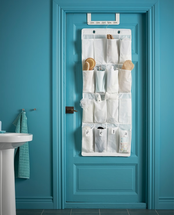 A bathroom door with hanging shoe organiser whose pockets hold brushes, hair sprays and other toiletries.