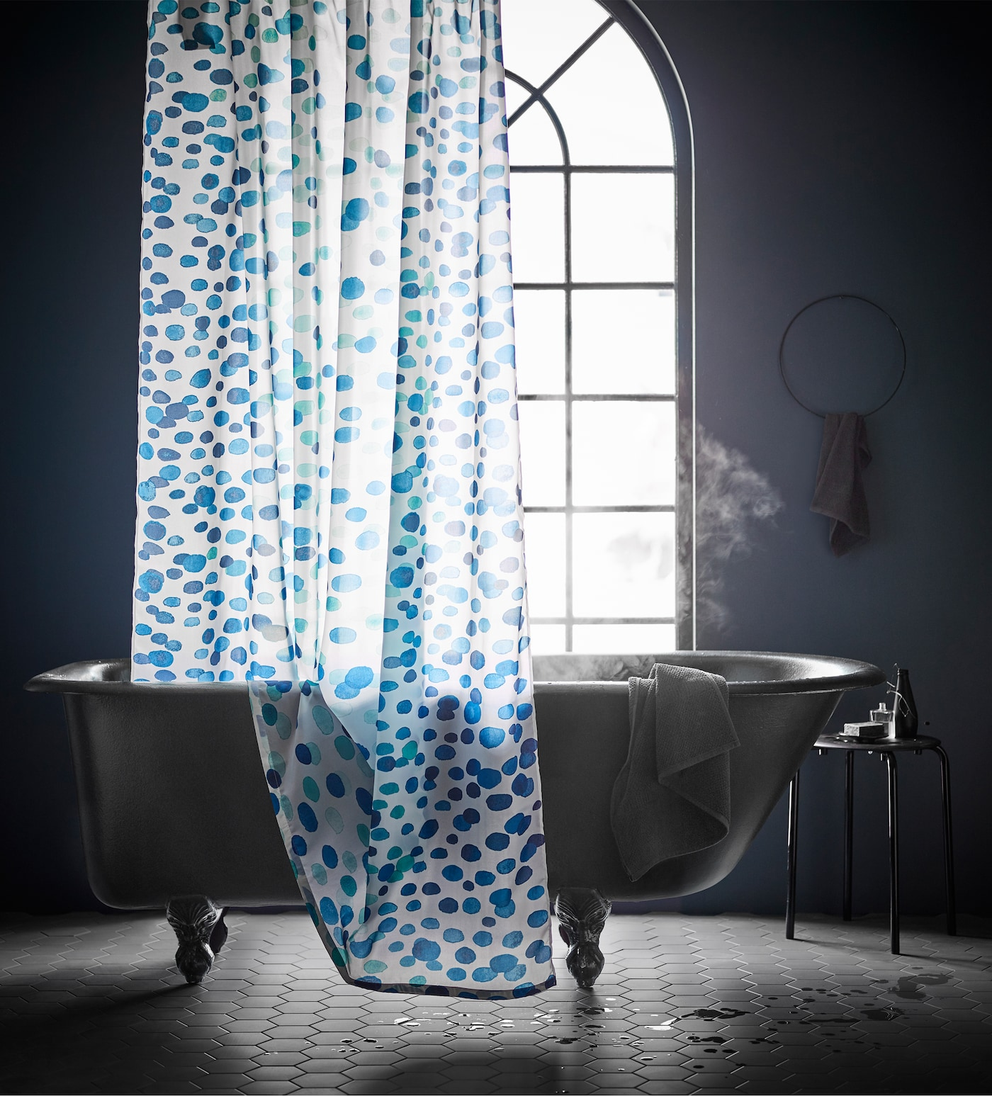 A bathroom with a bathtub on feet filled with hot water and a white shower curtain with splashes of blue and turquoise.