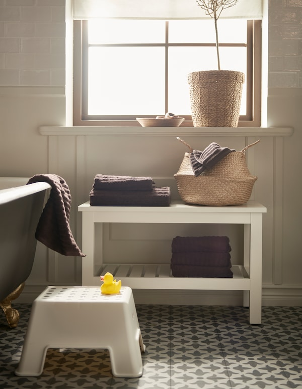 A bathroom with a rattan basket, a white BOLMEN step stool, and a white HEMNES bench with a shelf for towels.