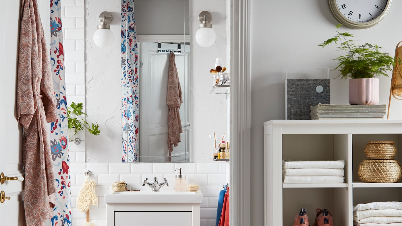 A bathroom with an EIDSÅ mirror, two FRIHULT white wall lamps, a storage unit with towels, sneakers and rattan baskets.