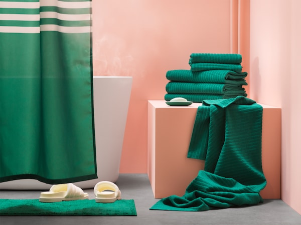 A bathroom with green walls, a grey floor, green bath towels and a green/white shower curtain.
