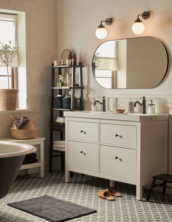 A bathroom with Moroccan style tiles and neutral colours, a HEMNES wash-stand with four drawers, and a large mirror.