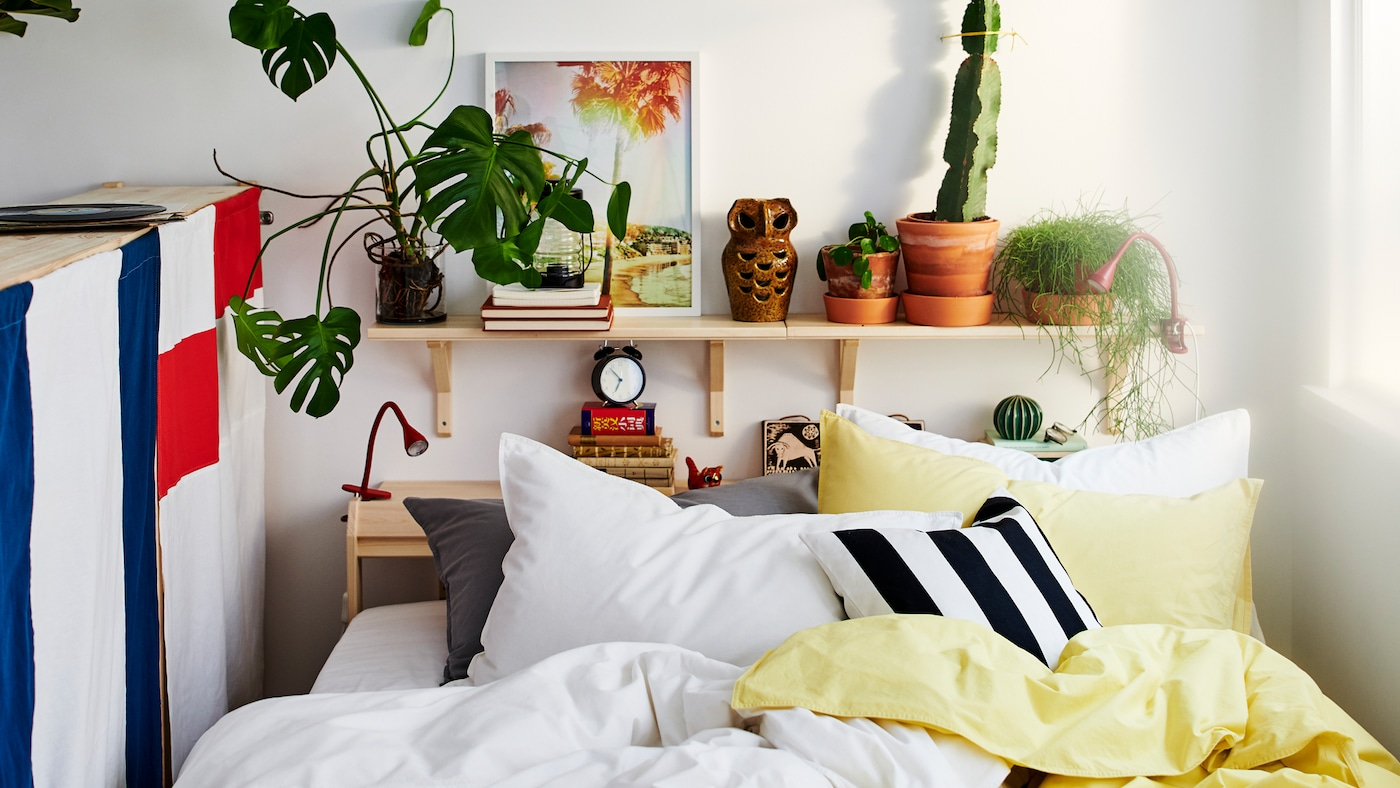 A bed between a window and the back of a storage unit with lots of pillows and yellow, white, black and grey bed linen.