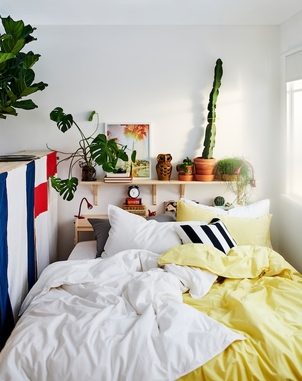 A bed between a window and the back of a storage unit with yellow, white, black and grey bed linen and lots of pillows.