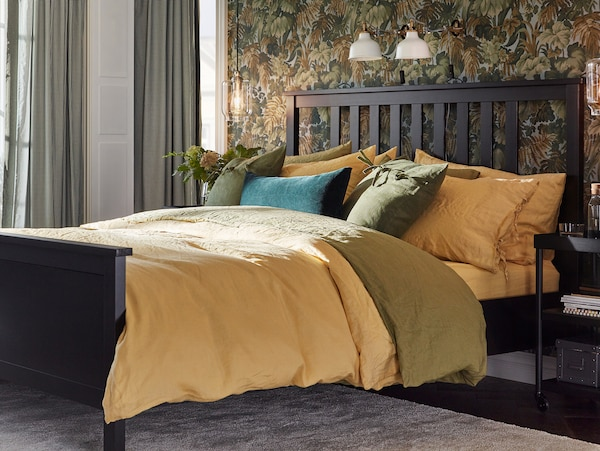 A bed made up with PUDERVIVA quilt covers and pillowcases in yellow and green, a yellow sheet and a cushion in green velvet.