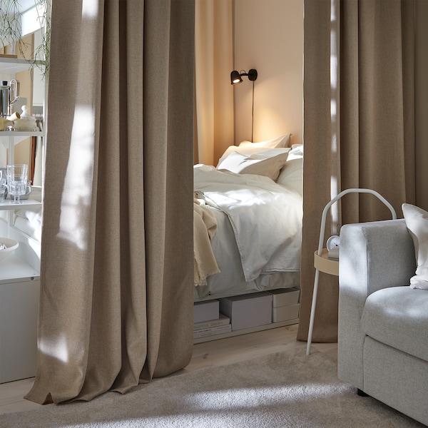 A bed that's slightly hidden behind beige curtains that surround it to create a cosy sleeping situation.