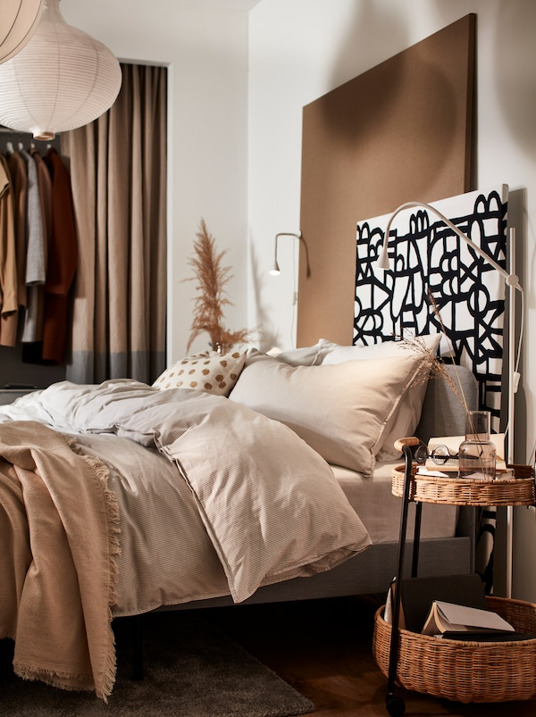 A bed with beige bed linen, and a wall panel made from particle board covered with black and white SKUGGBRÄCKA metre fabric.