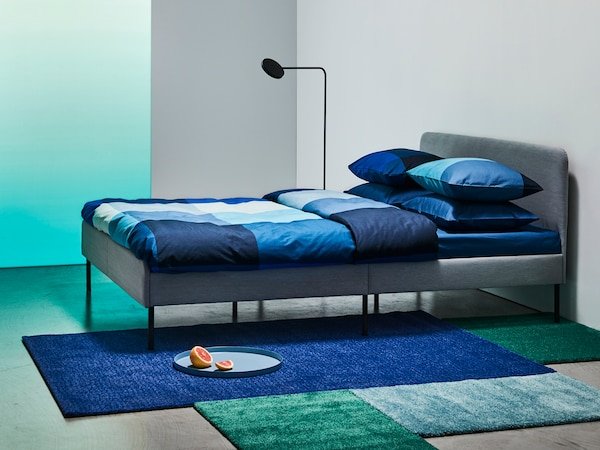 A bed with blue bed covers and blue pillow cases, in a room with a lamp and a blue mat beside the bed.