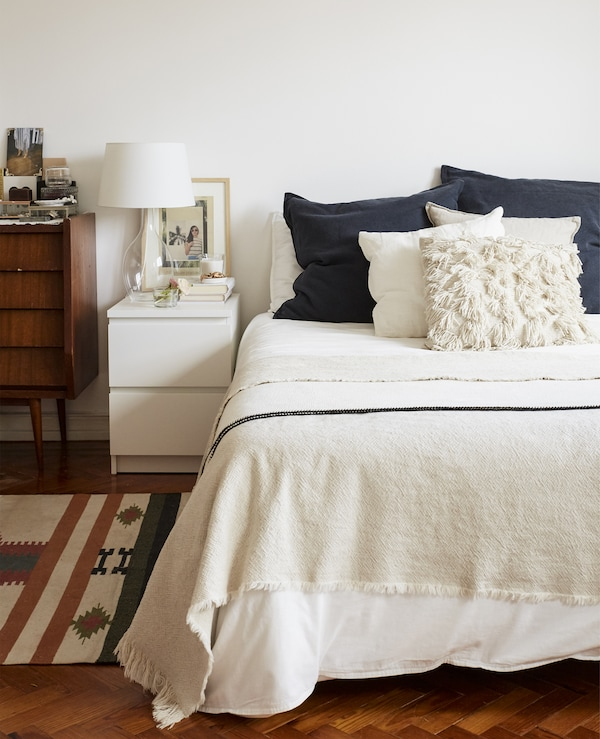 A bed with white bedding and navy cushions, a modern bedside table and a vintage cabinet.