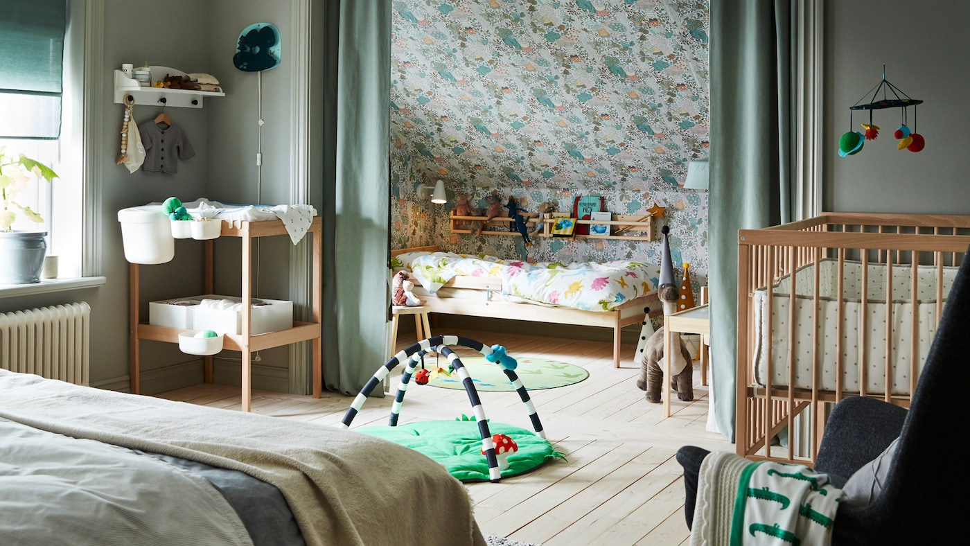 A bedroom containing a double bed, SNIGLAR cot, changing table and child's bed with rail, and curtains dividing the space.