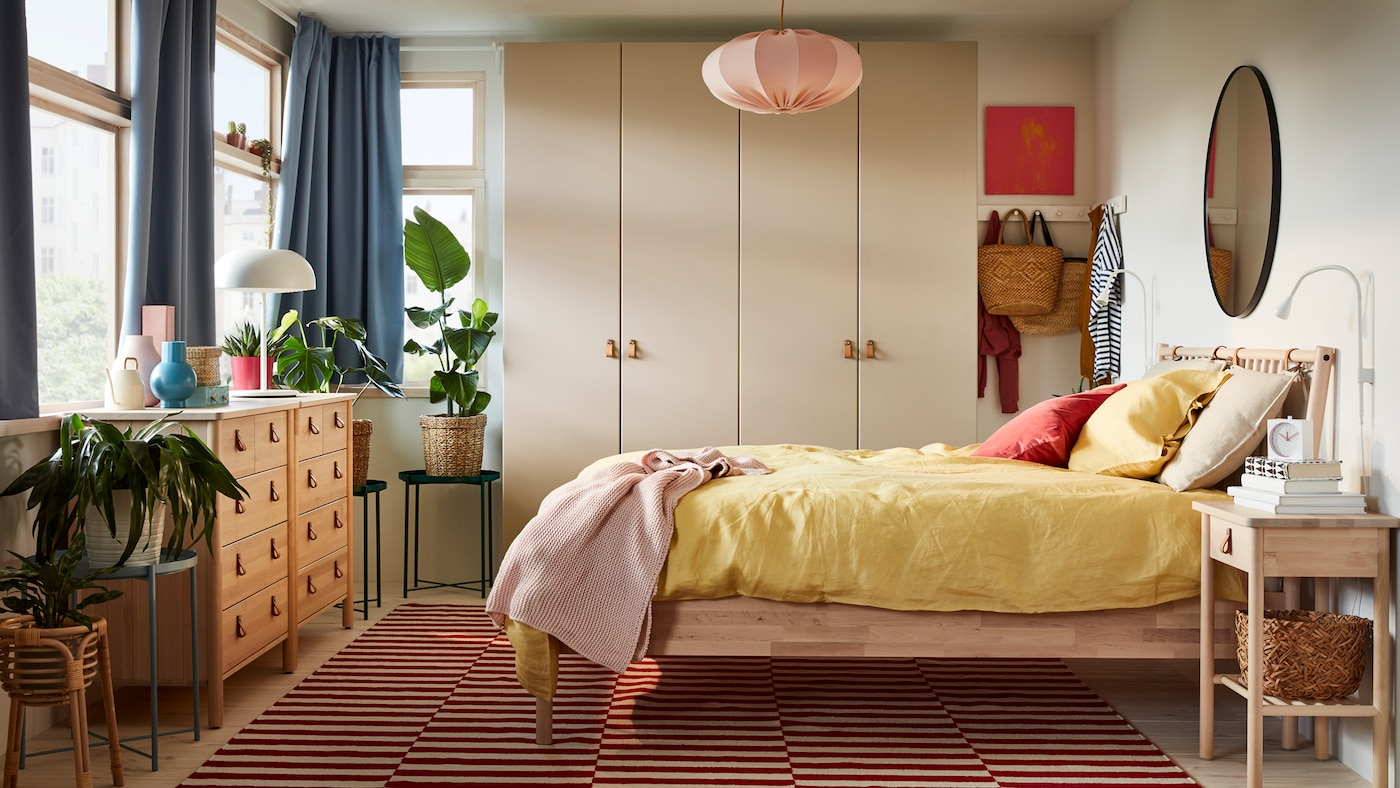 A bedroom containing BJÖRKSNÄS bed, chests of drawers and bedside table, with a PAX/REINSVOLL wardrobe and GLADOM tables.