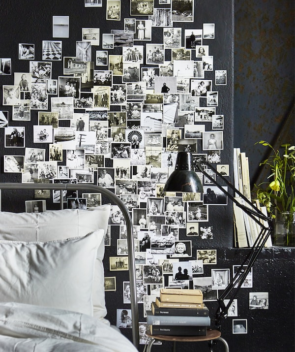 A bedroom wall covered in black and white family photos.