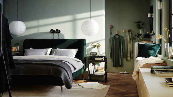 A bedroom with a green TUFJORD bed and two SKURUP lamps on the wall behind it. NORDLI drawer units run along the side wall.