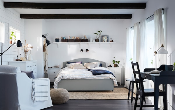 A bedroom with a traditional and coordinated style that has a beige HAUGA bed, a white armchair and a blue-green desk in it.