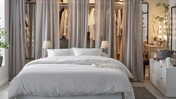 A bedroom with a white NORDLI bed, an open BOAXEL wardrobe with grey HILJA curtains in front, and NORDLI chests of drawers.